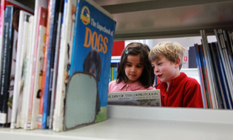 Photograph of North Ainslie students reading between bookshelves