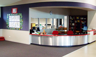 Photograph of North Ainslie bright coloured library desk with a sweeping curved metallic surface